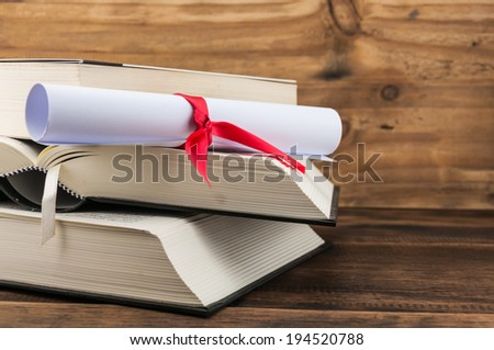 A parchment diploma scroll, rolled up with red ribbon on stack of book on wood background - stock photo