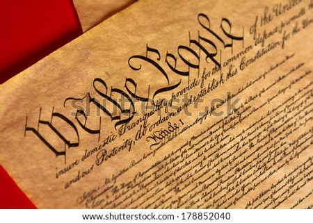 A parchment of the Constitution of the United States with a red background - stock photo