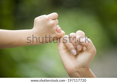 A Parent And The Child Hooking Their Fingers To Make A Promise - stock photo