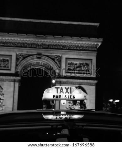 A Parisian taxi near Arc de Triomphe in Paris. Black and white. Aged photo. - stock photo