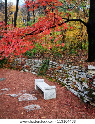 A Park Bench And Stone Wall Under The Brilliant Colors Of A Rainy Autumn Day, Southwestern Ohio, USA - stock photo