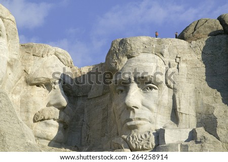 A park ranger and photographer standing above Abraham Lincoln at Mount Rushmore National Memorial, South Dakota - stock photo