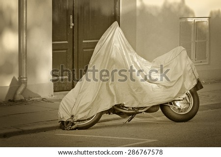 A parked scooter with protective cover at the street - stock photo