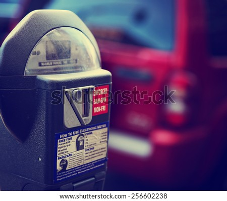 a parking meter with a car in the background on a city street downtown toned with a retro vintage instagram filter app or action effect - stock photo