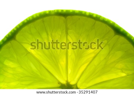 A part of a green lime slice, back lit and isolated on white background.