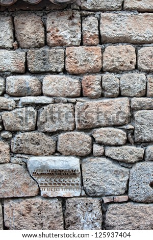 A part of an ancient roman building is used in a stone wall - stock photo