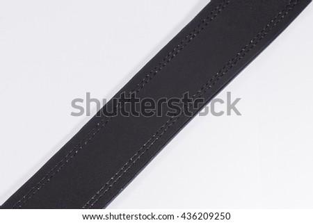 A Part of Black Leather Belt on White Background (Isolated Photo) - stock photo