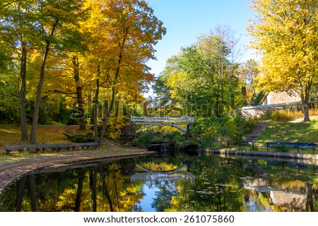 A part of Small Lake with reflection of trees in water, in a Park of Montreal in Autumn, and little Bridge in Background - stock photo