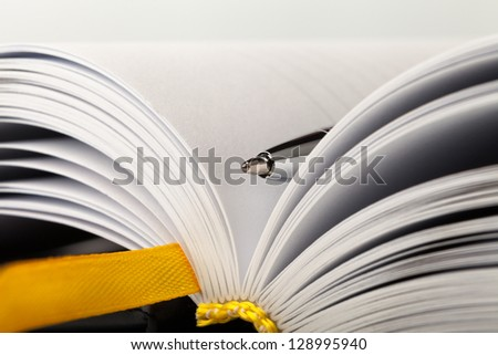 a part of the notepad with yellow bookmark and metal pen - stock photo