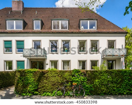 A part of typical austrian (german) three-storey house with a brown tile roof and green hedges building in a residential neighborhood. Old bicycle parking in front of it. - stock photo