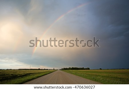 A partial rainbow with cloud cover over a gravel countryside road between fields of flowering canola in a dusk rural landscape