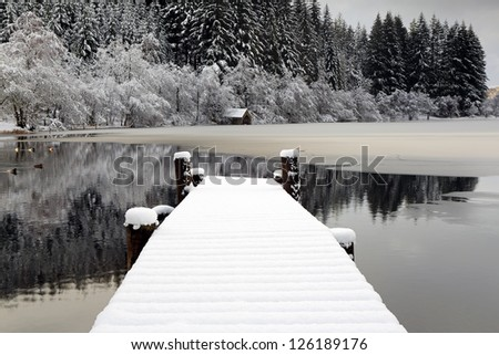 A partially frozen Loch Ard and snow covered jetty on a cold winter morning. Loch Lomond and the Trossachs national park, Scotland