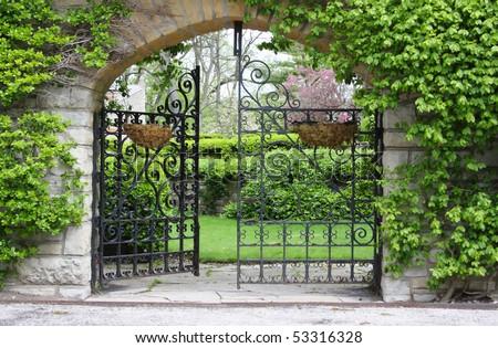 A partially open gate, entrance to a garden - stock photo