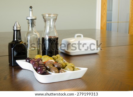 A party tray of mixed olives with a carafe of red wine, and bottles of balsamic vinegar and oil