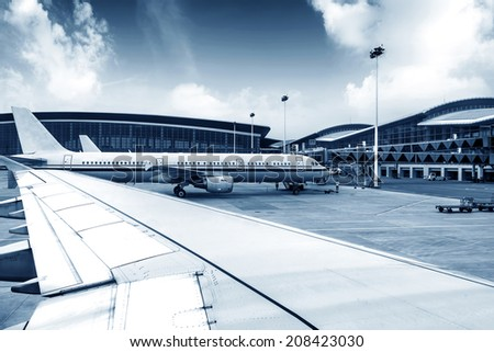 A passenger plane being serviced by ground services before next takeoff. - stock photo