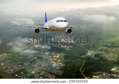 A passenger plane flying above the clouds in the sky over the city Saint-Petersburg - stock photo