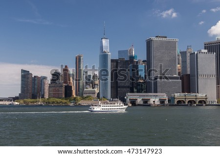 A passenger vessel is cruising in the New York harbor in front of office buildings of downtown Manhattan.