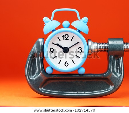 A pastel blue colored  alarm clock placed in a Grey clamp against a pastel orange background, asking the question do you manage your time effectively. - stock photo