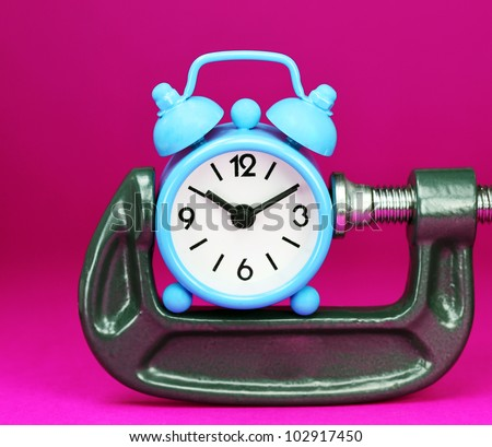 A pastel blue colored  alarm clock placed in a Grey clamp against a pastel purple background, asking the question do you manage your time effectively. - stock photo