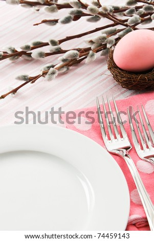 A pastel pink place setting is decorated for an Easter meal leaving ample copy space over a white plate. - stock photo