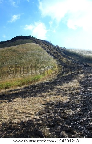 A path leading over the top of a grassy hill. - stock photo