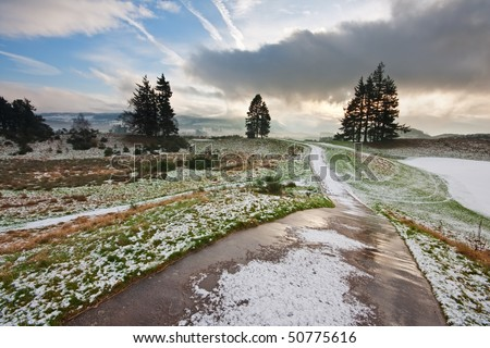 A path running through a snowy golf course on a winter morning in Scotland, with dramatic clouds in the background.