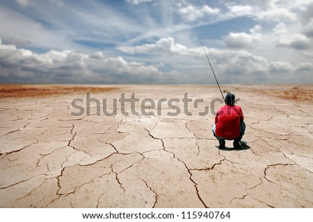 A patient angler fishing at a dried out lake for the concept of hoping for a better future. - stock photo