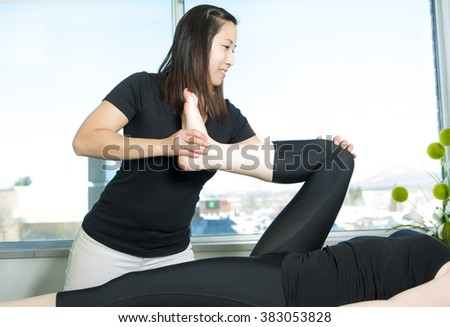 A Patient at the physiotherapy doing physical exercises with his therapist - stock photo