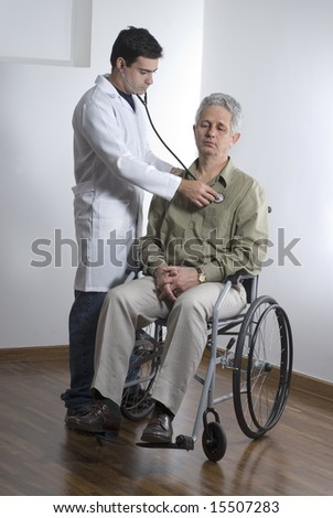 A patient is sitting in a wheelchair at a doctors office. Vertically framed shot.