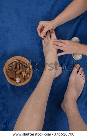 A patient receives a foot acupuncture - stock photo