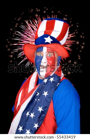A patriotic man dressed in red, white and blue with fireworks in the black sky.