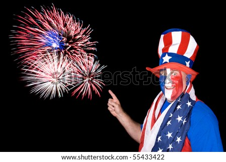 A patriotic man dressed up in red, white and blue points to fireworks in the sky.