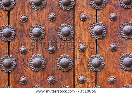 A pattern of metal flower-like decorations attached in rows to the surface of an old wooden door. - stock photo
