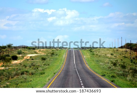 A paved road with green grass on the sides and blue sky above