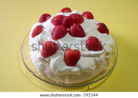 A pavlova desert with whipped cream and fresh strawberries on top - stock photo