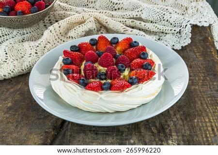A Pavlova dessert with vanilla cream and summer fruit on wooden table - stock photo