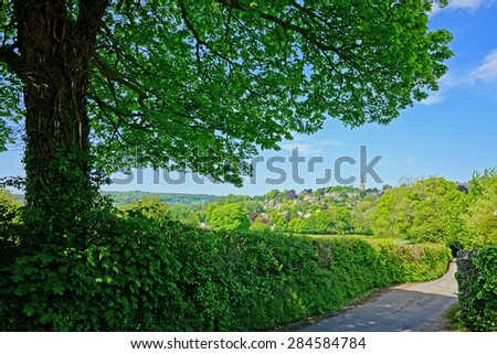 A peaceful Cotswold country lane in summer with a distant view of the village of Painswick, The Cotswolds, Gloucestershire, United Kingdom - stock photo