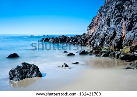 A peaceful image of shoreline scenery in Laguna Beach California.  Image shot to capture the motion of the water. - stock photo