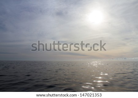 A peaceful ocean scene with sunlight reflecting across the ocean and dreamy clouds