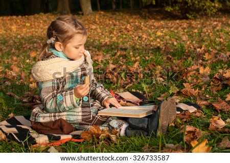 A peaceful outdoor portrait of a little girl sitting on a blanket and reading a book in a park, a lot of golden fallen leaves around