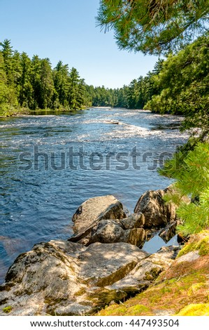 A peaceful scene of a river running from Cascade Falls in the Boundary Waters Canoe Area, in the remote North Woods of Northern Minnesota with blue skies and green trees.  - stock photo
