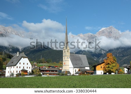 A peaceful village by Hochkoenig Mountains in Austria ~ Beautiful scenery of a church tower (Wallfahrtskirche) standing tall in a green meadow with foggy mountains in the background in Maria Alm - stock photo