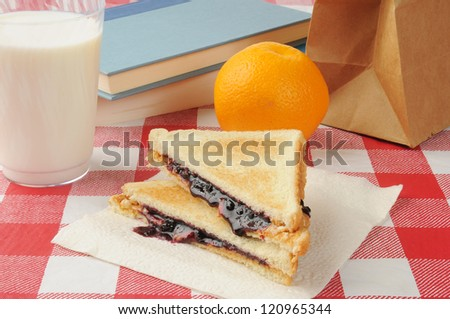 A peanut butter and jelly sandwich as a school lunch - stock photo