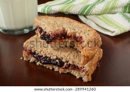 A peanut butter and jelly sandwich with a bite out of it - stock photo