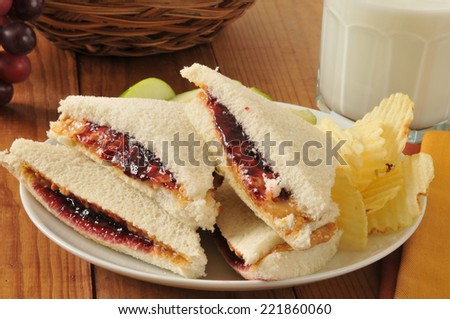 A peanut butter and jelly sandwich with the crust trimmed off - stock photo