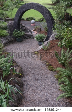 A pebble walkway leads through a stone circle to a curved path maze with a large stone sphere in the center. Other smaller spheres surround it, symbolic of personal exploration and enlightenment. - stock photo
