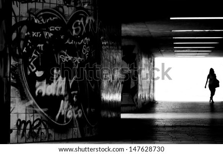A pedestrian crosses a dark, tiled tunnel with graffiti on the walls/In the dark tunnel                - stock photo