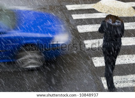 a pedestrian crossing a road in a snowing weather