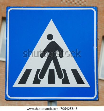 A pedestrian crosswalk is designated in Italy with this character sign.  No words are needed to convey the message on the streets of Camucia.