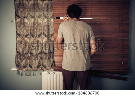 A peeping tom is looking out through his blinds  - stock photo